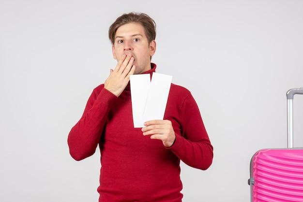 Vista frontal de los hombres jóvenes con billetes de avión sobre fondo blanco.