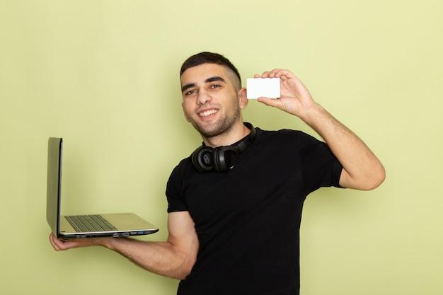 Vista frontal de los hombres jóvenes en camiseta negra sonriendo y usando la computadora portátil que muestra la tarjeta blanca en verde