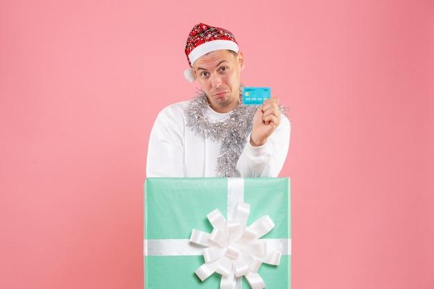 Vista frontal de los hombres jóvenes dentro del presente con tarjeta bancaria en el fondo de color rosa
