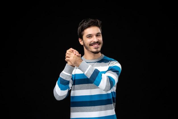 Vista frontal de los hombres jóvenes en jersey de rayas azules sonriendo en la pared negra