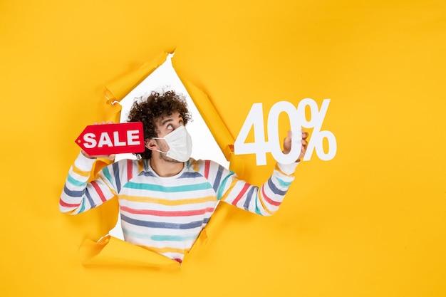 Vista frontal de los hombres jóvenes en máscara sosteniendo la escritura en amarillo comercial salud pandemia covid- virus foto venta color