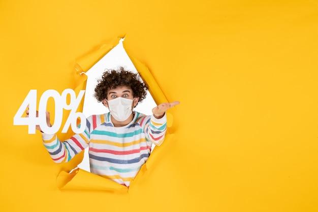 Vista frontal de los hombres jóvenes en máscara sosteniendo la escritura sobre el virus de la salud amarillo covid pandémico- foto venta color
