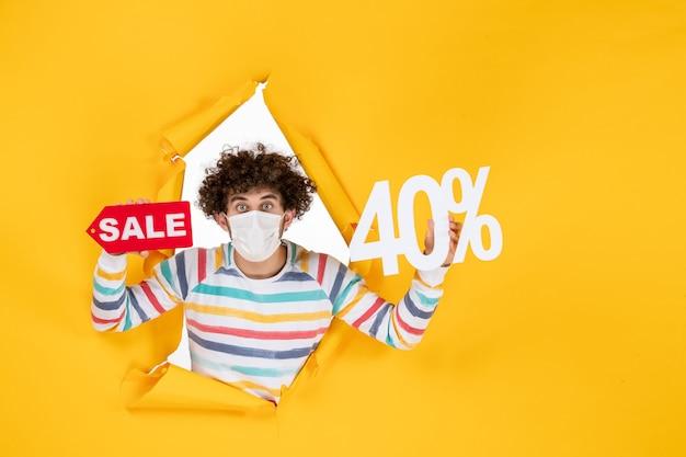 Vista frontal de los hombres jóvenes en máscara sosteniendo la escritura sobre el virus de la salud amarillo pandemia de compras covid- foto venta color rojo