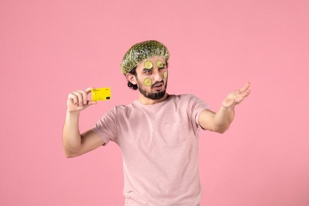 Vista frontal de los hombres jóvenes con máscara en su rostro sosteniendo una tarjeta bancaria sobre fondo rosa