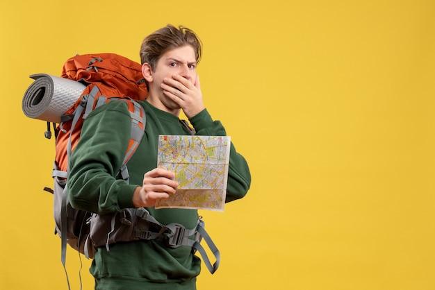 Vista frontal de los hombres jóvenes preparándose para el senderismo con mapa