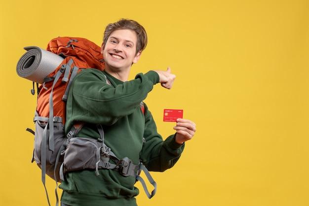 Vista frontal de los hombres jóvenes preparándose para el senderismo con tarjeta bancaria