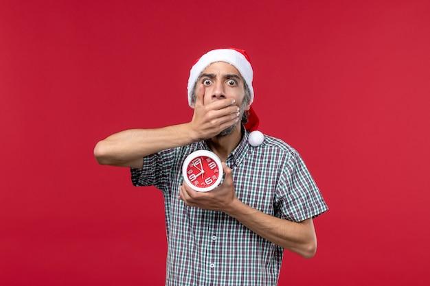 Vista frontal de los hombres jóvenes con relojes redondos en el escritorio rojo