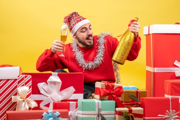 Vista frontal de los hombres jóvenes sentados alrededor de regalos celebrando con champán sobre fondo amarillo
