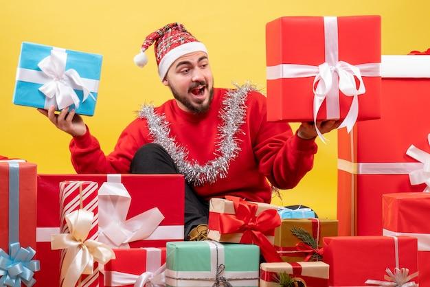 Vista frontal de los hombres jóvenes sentados alrededor de los regalos de navidad en amarillo
