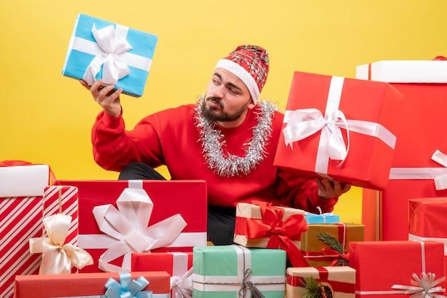 Vista frontal de los hombres jóvenes sentados alrededor de los regalos de navidad sobre fondo amarillo