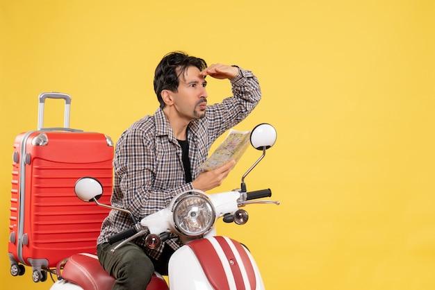 Vista frontal de los hombres jóvenes sentados en bicicleta y observando el mapa mirando a distancia en amarillo