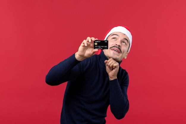 Vista frontal de los hombres jóvenes con tarjeta bancaria negra sobre fondo rojo.