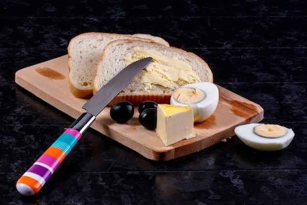 Vista frontal huevo cocido a bordo con aceitunas y rebanadas de pan con mantequilla y un cuchillo