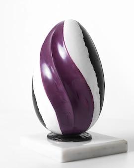 Vista frontal de huevo de color púrpura blanco y negro forrado en el piso blanco