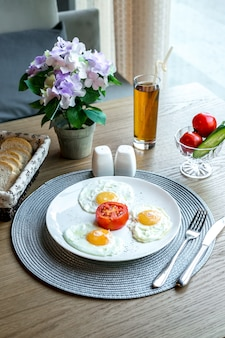 Vista frontal huevos fritos con tomate en un plato con un refresco y flores en una olla sobre la mesa