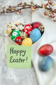 Vista frontal de los huevos de pascua de color dentro de la caja en forma de corazón sobre fondo blanco colorido concepto de pascua primavera ornamentado novruz