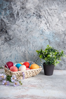 Vista frontal de huevos de pascua de colores con una bonita caja diseñada sobre fondo blanco grupo de primavera coloridos colores ornamentales
