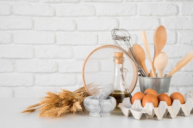 Vista frontal huevos con utensilios de cocina
