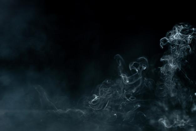 Vista frontal del humo blanco de la vela sin fuego en la pared oscura