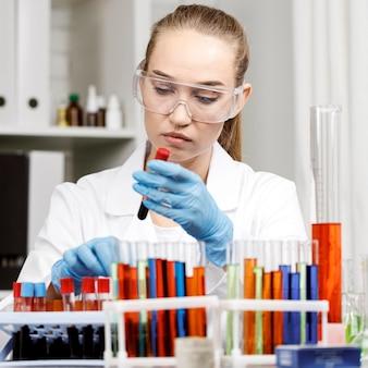 Vista frontal de la investigadora con guantes y tubos de ensayo en el laboratorio