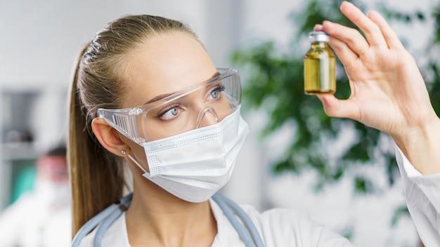 Vista frontal de la investigadora con máscara médica y vacuna