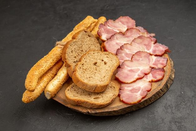 Vista frontal de jamón fresco en rodajas con rebanadas de pan y bollos en carne de color oscuro comida