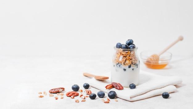 Vista frontal jarra llena de leche y frutas
