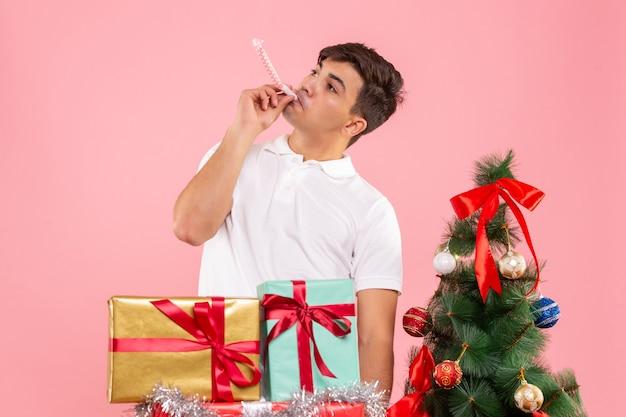 Vista frontal joven alrededor de regalos de navidad y árbol de vacaciones en el fondo rosa