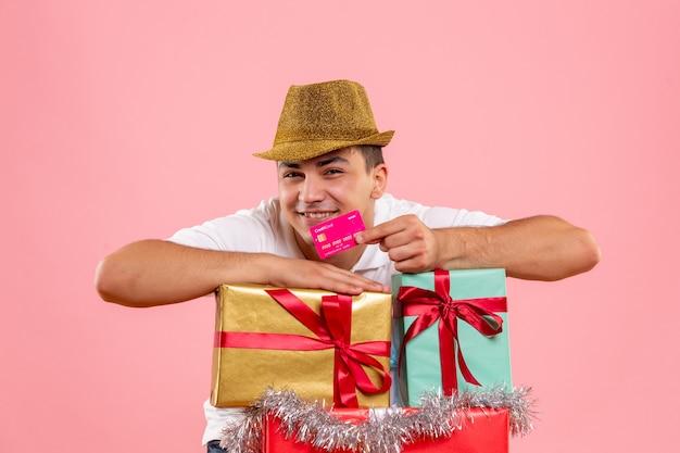 Vista frontal del joven alrededor de regalos de navidad con tarjeta bancaria en la pared rosa