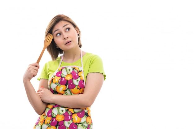 Una vista frontal joven ama de casa hermosa en camisa verde capa colorida sonriendo sosteniendo cocina aparato de madera pensando en el fondo blanco limpieza de la cocina de la casa
