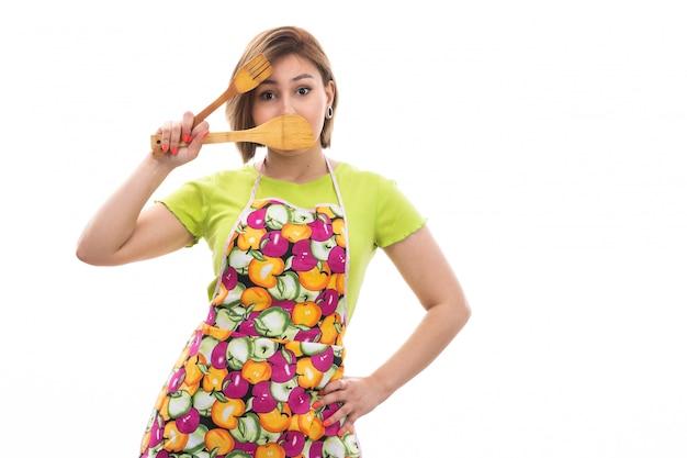 Una vista frontal joven ama de casa hermosa en camisa verde capa colorida sonriendo sosteniendo electrodomésticos de cocina de madera sobre el fondo blanco limpieza de la casa cocina