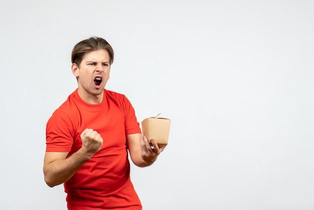 Vista frontal del joven ambicioso y emocional en blusa roja sosteniendo una pequeña caja sobre fondo blanco.