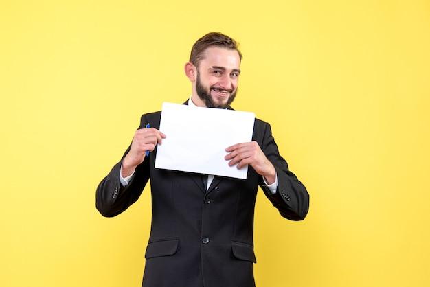 Vista frontal del joven apuesto joven empresario sonriendo y sosteniendo un papel blanco en blanco con un bolígrafo en amarillo
