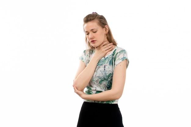 Una vista frontal joven atractiva en camisa diseñada y falda negra que sufre de dolor de garganta en el blanco