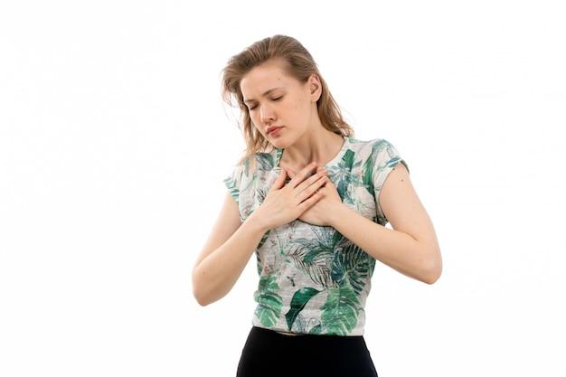 Una vista frontal joven atractiva en camisa diseñada y pantalón negro que sufren de problemas respiratorios en el blanco