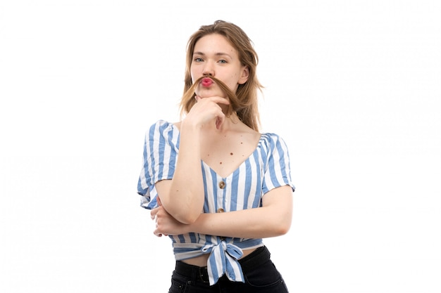 Una vista frontal joven atractiva en camiseta a rayas azul-blanca con jeans negros posando con barba en el blanco