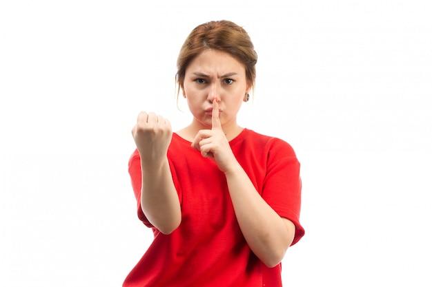Una vista frontal joven atractiva en camiseta roja con jeans negros amenazando silencio con el puño en el blanco
