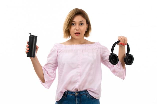 Una vista frontal joven y atractiva dama en camisa rosa y jeans azul con auriculares negros bebiendo con termo negro auriculares negros en el blanco
