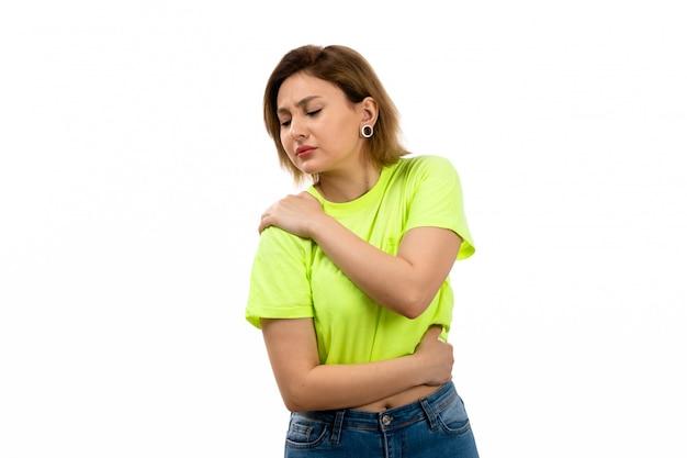 Una vista frontal joven y atractiva dama en camisa verde y jeans azul que sufren de dolor de hombro en el blanco