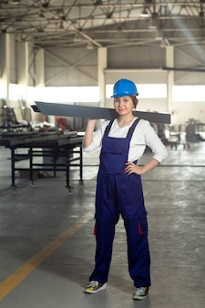 Una vista frontal joven y atractiva dama en traje azul de construcción y casco trabajando sosteniendo algo pesado metálico durante la construcción de arquitectura de edificios diurnos