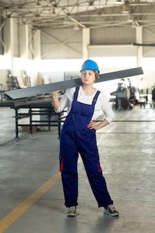 Una vista frontal joven y atractiva dama en traje azul de construcción y casco de trabajo sosteniendo pesados detalles metálicos durante la construcción de arquitectura de edificios durante el día