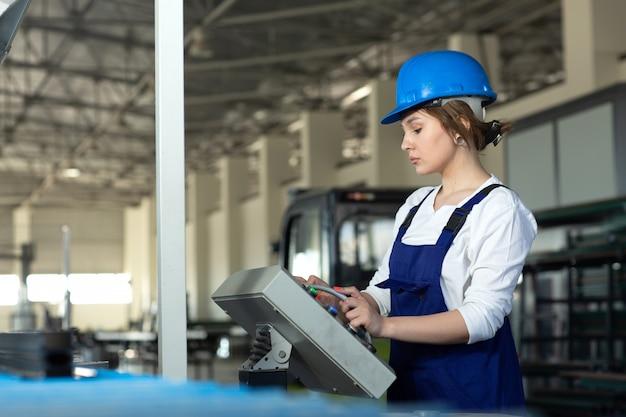 Una vista frontal joven y atractiva dama en traje azul de construcción y máquinas de control de casco en hangar trabajando durante la construcción de arquitectura de edificios diurnos