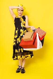 Una vista frontal joven y atractiva dama en vestido de flores amarillas y negras con un vendaje amarillo en la cabeza sonriendo sosteniendo paquetes de compras en el amarillo