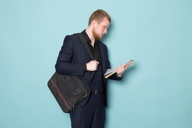 Una vista frontal joven atractivo masculino con barba en negro oscuro clásico moderno traje moderno con archivos mochila en el espacio azul
