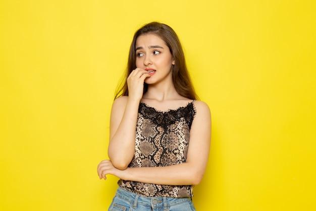 Una vista frontal joven y bella dama en blusa marrón y jeans azul con pose preocupada