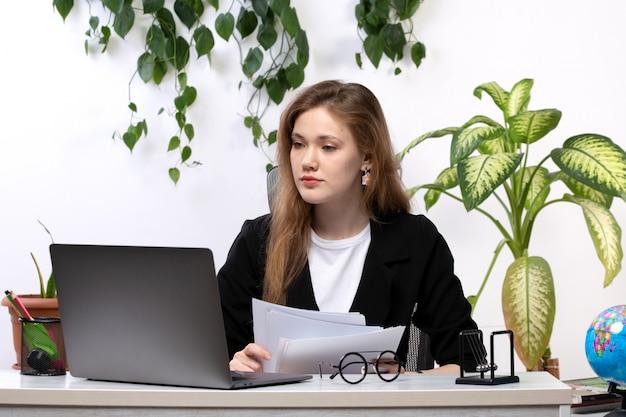 Una vista frontal joven bella dama en camisa blanca y chaqueta negra trabajando con documentos usando su computadora portátil frente a la mesa con hojas colgando