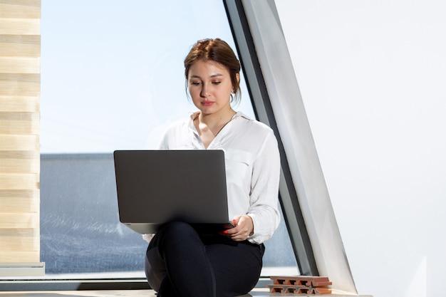 Una vista frontal joven bella dama en camisa blanca pantalón negro sentado cerca de la ventana trabajando en la computadora portátil durante el día durante la actividad laboral del edificio