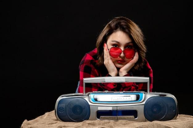 Una vista frontal joven y bella dama en camisa a cuadros rojo-negro con gafas de sol rojas cerca de la grabadora