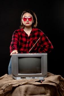 Una vista frontal joven bella dama en camisa a cuadros rojo-negro en gafas de sol rojas cerca de little tv