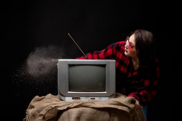 Una vista frontal joven y bella dama en camisa a cuadros rojo-negro con gafas de sol rojas cerca de la pequeña televisión soplando polvo